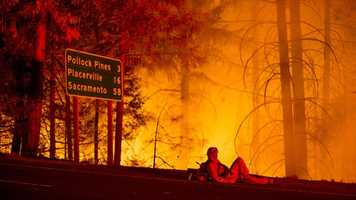 A firefighter battling the King Fire watches a backfire burn along Highway 50 in Fresh Pond, California, on Tuesday night.