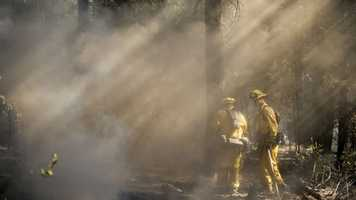 Firefighters checking for hotspots are seen through a haze of smoke near Fresh Pond, California.