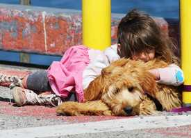 A girl rests with her dog while her parent fish from the Monterey Wharf.
