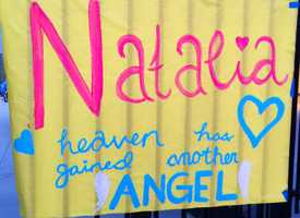 "A sign reads, ""Natalia. Heaven has gained another angel."""