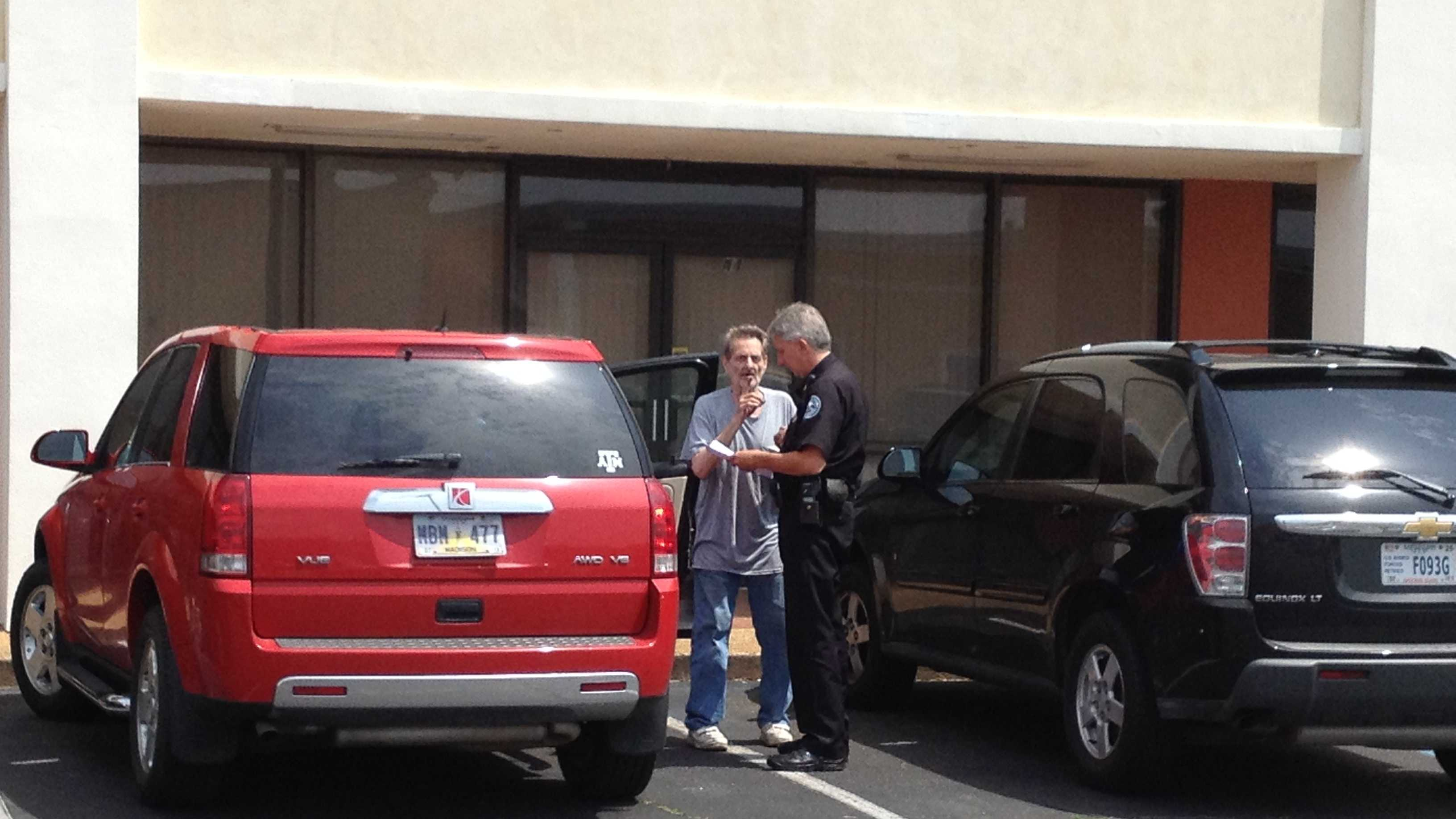 Paul White speaks to a Jackson police officer at Precinct 4.