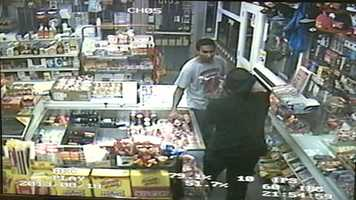 The robber points a gun at the clerk.