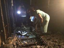 Investigators sift through debris searching in an effort to find out what started the fire on Will-O-Wood Boulevard.