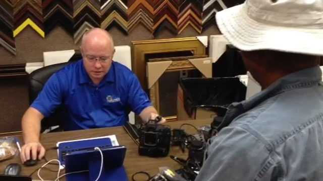 Edward Whitesides, of KEH Cameras, pays Adrian Delano $800 for his old cameras and gear.