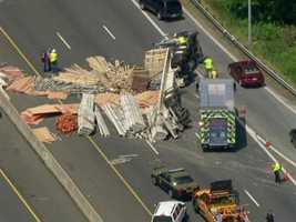 The tractor-trailer overturned and lost its load of lumber and pipes around 12:45 p.m. Thursday near Exit 11.