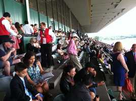 Racing fans converge at the Churchill Downs grandstand for the 144th Belmont Stakes.