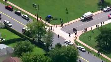 Police, students and parents swarm the school after a student reportedly brought a gun into the school's cafeteria and fired off two shots.