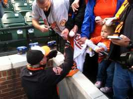 Buck Showalter signs autographs before the start of Game 1 of the ALDS.