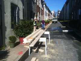 City crews bring in lumber to stabilize two homes that have just been condemned.