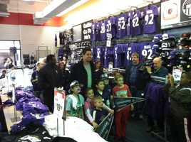 Dennis Pitta posing for pictures with fans as he picks up AFC Championship gear.