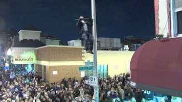 A man dangerously climbs up a light pole and tries to do pull-ups off part of it that was sticking out.