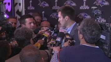 Flacco is flanked by reporters at the event.