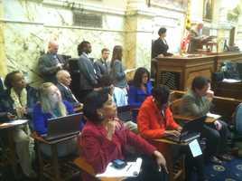 Members of the media listen to the debate.