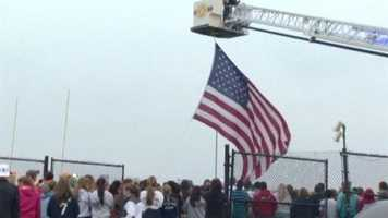The vigil started with a moment of silence as a Kent Island volunteer fire truck raised a flag above the stadium. Mourners lit candles and prayed for the teens, their families and the community.