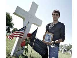 Allaert takes a photo by 112th IR Sgt. Emmett P. Clark's grave, which he adopted, at the memorial. He went on to contact Clark's living family members and forwarded them relics he has found over the years on the former battlefield. Read the story