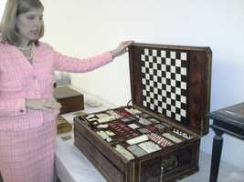 This is a game board from the era that includes checkers, chess and other games. At the time, it was considered a luxury item and so only very few families could afford one.