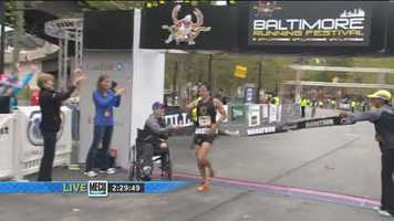 Dave Berdan crosses the finish line well ahead of everyone else to win the 2013 Baltimore Marathon.