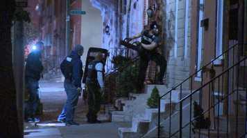 Police break down a door during the raids.