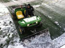 Mini snowplows clearing snow off the field at M&T Bank Stadium