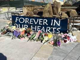 Flowers are placed at an outdoor memorial at the mall.
