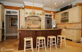 The gourmet kitchen features a butler's pantry, a breakfast bar, island and table space.