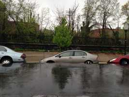 A block-long portion of 26th Street collapses Wednesday, swallowing cars in Charles Village.