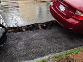 A giant crack can be seen in the road where the pavement is giving way.