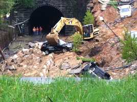 Crews begin Thursday removing cars that fell onto the train tracks during the massive landslide.