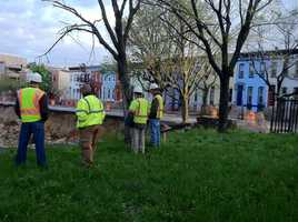 Crews look at the collapse site as the evacuated homes sit empty in the background.