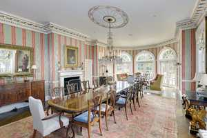 The home boasts a conservatory with vaulted ceilings and a hand-painted trompe l'oeil mural, as well as a 22-seat formal dining room with a signed Perry of London crystal chandelier, pictured here.