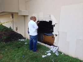 County inspectors check out the structural integrity of the building after the SUV is removed.