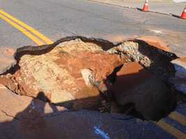 Officials said a 12-inch water main broke Friday morning along a section of Industry Lane.  That break then led to a large sinkhole forming in the roadway.