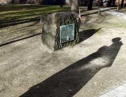 Shadows of visitors are seen in front of Samuel Adams' grave site at the Old Granary Burying Ground.