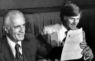 Orr holds a multi-million dollar contract with the Chicago Blackhawks at a signing ceremony on June 24, 1976