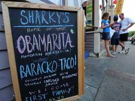 People wait to get in a restaurant as it displays a board naming drinks after Barack Obama in Oak Bluffs.