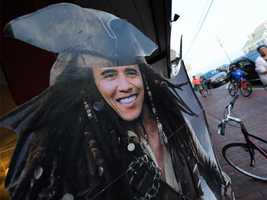 People walk past a cut-out depicting Obama as the Pirate of the Caribbean in front of a store in Oak Bluffs