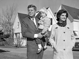 Sen. John F. Kennedy, Democrat presidential nominee, is shown with his wife, Jacqueline, as he holds their daughter, Caroline, outside their home in Hyannis Port, on Nov. 8, 1960.