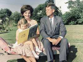 Jacqueline Kennedy reads to daughter Caroline outside their home in Hyannis Port, on July 25, 1960.