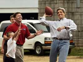 Kerry tosses a football with Rep. Ron Kind and his son Johnny at the Dejno Acres dairy farm in Independence, Wis., July 3, 2004.