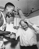 Celtics coach Red Auerbach takes a shower with his clothes on as Bill Russell adds a little persuasion after Boston won its seventh consecutive NBA championship.