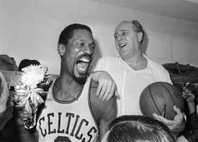 Russell holds a corsage sent to the dressing room as he celebrates with Red Auerbach after defeating the Lakers to win their eighth-straight NBA title, April 29, 1966