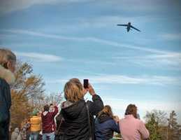 A military transport plane flies over Plymouth before the start of the parade.