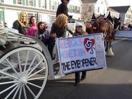 Dorothy grabbing a News Center 5 sign along the parade route.