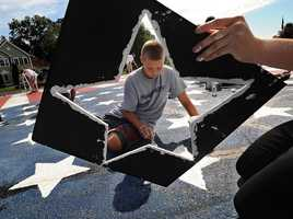 Jared Leahy, 12 is framed by a stencil of a star while repainting an American flag.