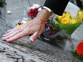 A woman reaches out to touch a name on a memorial to Massachusetts victims of 9/11.