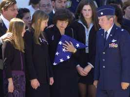 Margaret Ogonowski, the widow of American Airlines pilot John Ogonowski, is surrounded by her daughters, from left, Mary, 11, Caroline, 14, and Laura, 16, right, after receiving a U.S. flag during a memorial service in Dracut.