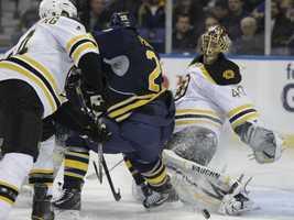 Boston Bruins goalie Tuukka Rask, right, watches the puck under pressure from Buffalo Sabres' Jason Pominville (29) as Bruins' Dennis Seidenberg (44) defends.