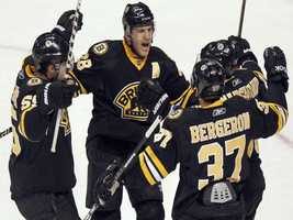 From left, Boston Bruin's Johnny Boychuk (55), Mark Recchi (28), Patrice Bergeron (37) and Brad Marchand (63) come together to celebrate Recchi's goal during the first period of an NHL hockey game against the Colorado Avalanche, Saturday, Jan. 22, 2011, in Denver.