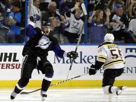 Tampa Bay Lightning's Steven Stamkos celebrates after scoring a goal as Boston Bruins' Johnny Boychuk looks on.