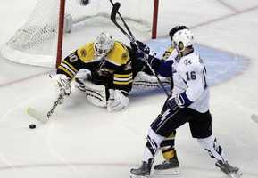 Boston Bruins goalie Tim Thomas makes a save in front of Tampa Bay Lightning right wing Teddy Purcell.